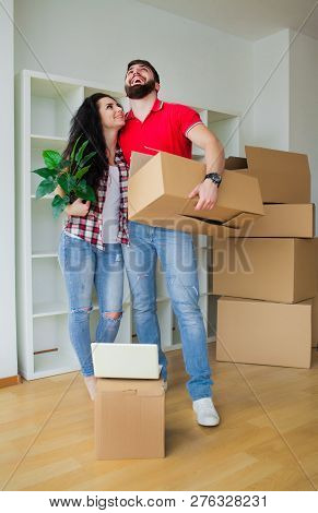 Young Couple Unpacking Cardboard Boxes At New Home.moving House