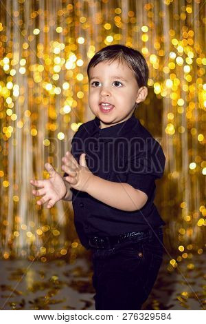 boy in black clothes at Christmas standing in a room on a background poster
