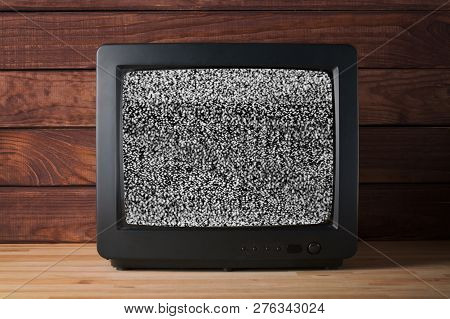 Old Vintage Tv Set Televisor On Wooden Table Againt Dark Wooden Wall Background With No Signal Telev