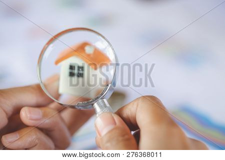 Close-up Of A Businessperson's Hand Looking At House Model Through Magnifying Glass, House Searching