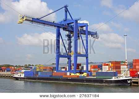 Hoisting crane with cargo ship in harbor of Rotterdam the Netherlands