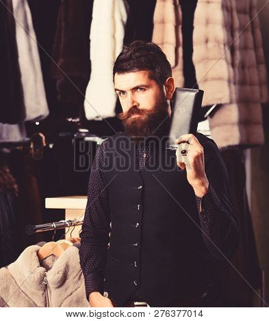 Guy with thoughtful face holds wallet. Macho with wallet in front of luxury furry clothes. Luxury clothing concept. Man with beard and mustache in fur shop. poster