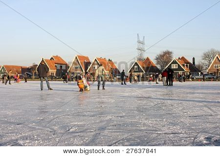 Ice skating in the countryside from the Netherlands with view on a dutch village