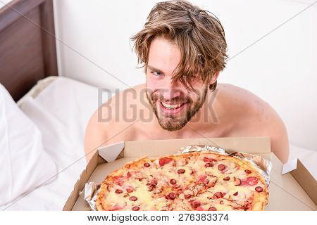 Guy Holds Pizza Box Sit Bed In Bedroom Or Hotel Room. Student Is At Home On The Bed In A Bright Apar