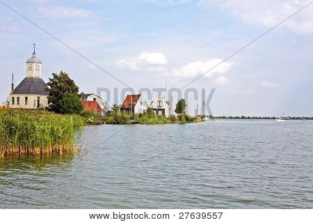Typical dutch: At Durgerdam,church and houses from wood along the IJsselmeer in the Netherlands