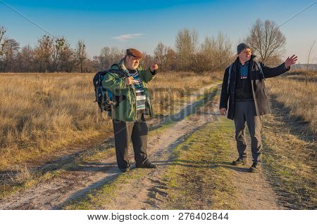Two Senior Hikers With Backpacks Discussing Correct Path While Walking On A Country Road At Autumnal