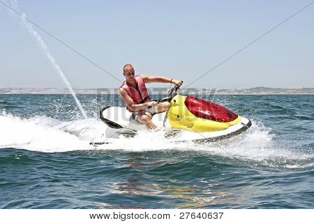 Young guy cruising on the atlantic ocean on a jet ski poster