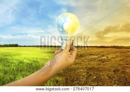Human Hands Holding Earth Inside The Light Bulb With Climate Change On The Background. Global Awaren