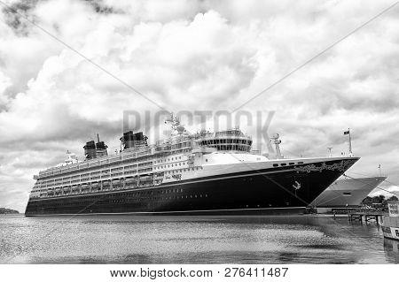 St Johns, Antigua - January 15, 2016: Disney Wonder Cruise Ship Docked At Sea Port On Cloudy Sky. Di