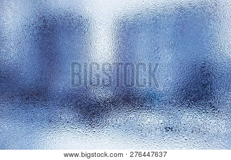 Wet Glass In Drops Of Rain. Wet Background Of Blue.the Texture Of The Wet Glass