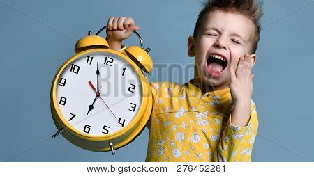 Cute Little Boy With Alarm Clock,isolated On Blue. Funny Kid Yawning Pointing At Alarm Clock At 7 Oc