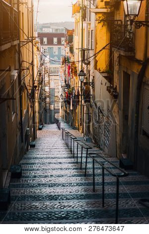 Beautiful Staircase In Lisbon. Hanging Laundry In Typical Narrow Street. Sunset In The Old Downtown
