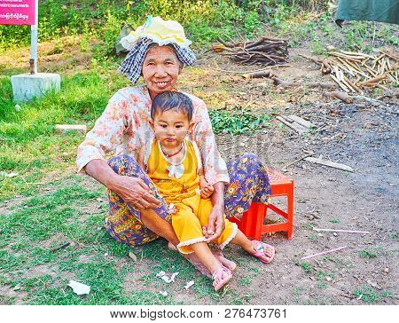 Ava, Myanmar - February 21, 2018: Portrait Of The Farmers Family - Grandmother With Little Girl, Sit