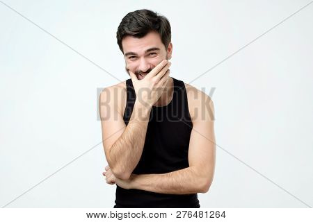 Young Man Laughing And Covering His Mouth With Hand Trying To Hold A Laugh