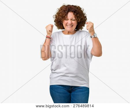 Beautiful middle ager senior woman wearing white t-shirt over isolated background excited for success with arms raised celebrating victory smiling. Winner concept.