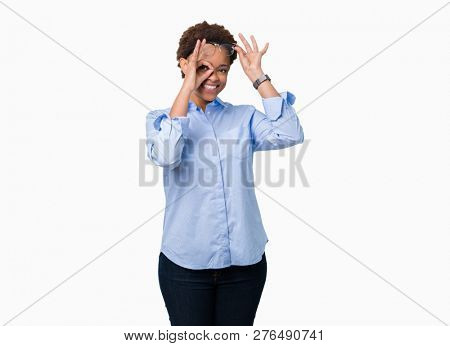Young beautiful african american business woman over isolated background doing ok gesture with hand smiling, eye looking through fingers with happy face.