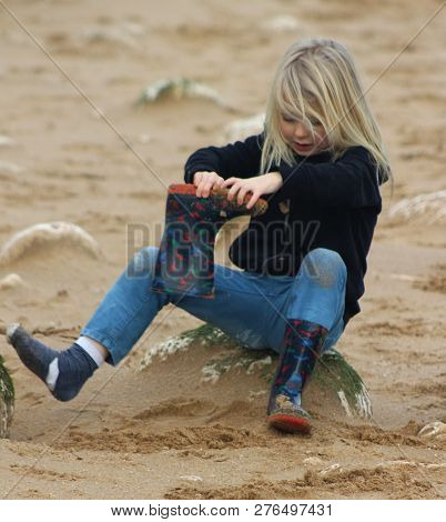 Child On Beach Taking Off Wellies And Emptying Out Sand