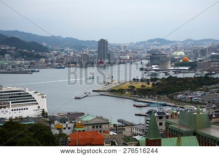 Nagasaki, Japan - October 26, 2018: Nagasaki port with ferries and cruiseboats surrounded by mountains