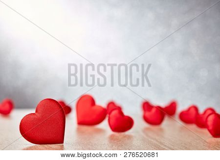 Valentine background with red satin hearts. Selective focus on big heart. Valentine's Day card with copy space. Design element for romantic greeting card, wedding invitation, Women's Day postcard