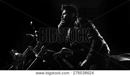 Night Racer Concept. Man With Beard, Biker In Leather Jacket Sitting On Motor Bike In Darkness, Blac