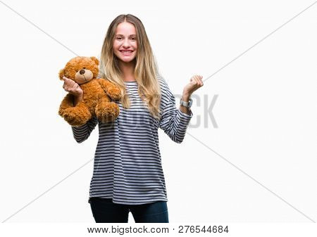 Young beautiful blonde woman holding teddy bear plush over isolated background screaming proud and celebrating victory and success very excited, cheering emotion