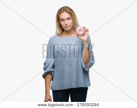 99418f76764 Young caucasian woman eating sweet donut over isolated background with a confident  expression on smart face