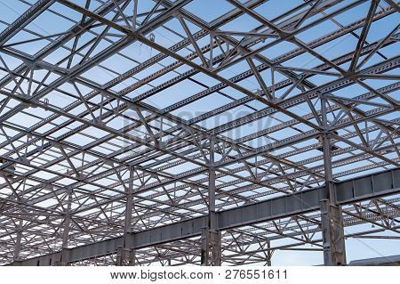 Metal Beams At The Top Of The Unfinished Steel Structure Of The Building Under Construction, Against