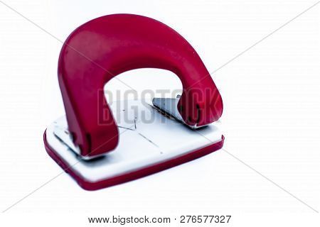 Close Up Of Red And White Colored Paper Punching Machine Isolated On White.