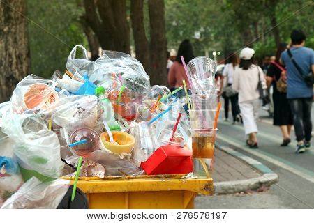 Garbage Plastic Waste Trash Full Of Trash Bin Yellow And Background People Are Walking On The Sidewa