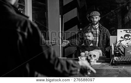 Hipster Client Got New Haircut. Reflexion Of Barber With Bearded Man Looking At Mirror, Dark Backgro