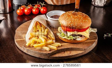 The Concept Of Italian Cuisine. Italian Burger With French Fries On A Wooden Board And A Glass Of Li