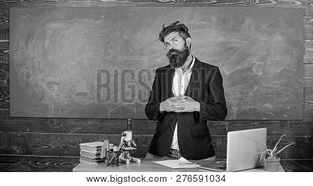 Teacher bearded man tell interesting story. Teacher interesting interlocutor best friend. Teacher charismatic hipster stand near table classroom chalkboard background. Talking to students or pupils. poster