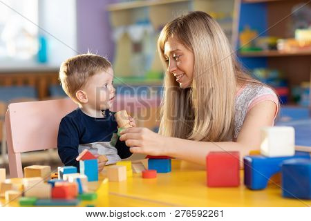 Cute Kindergarten Teacher And Baby Toddler Playing Educational Toys At Creche Or Nursery