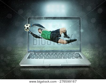 Caucassian soccer Player in dynamic action with ball in a professional sport game play on the laptop in football under stadium lights.
