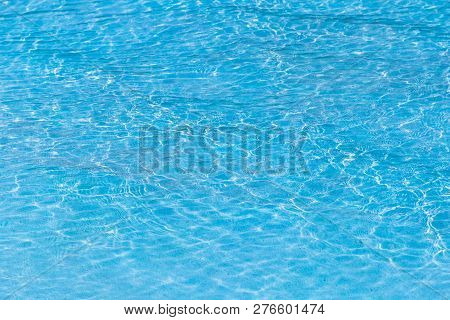 Blue Ripped Water In Swimming Pool With Sunny Reflections.