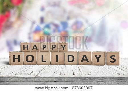 Happy Holidays Sign Made Of Wooden Toy Cubes With A Winter Landscape In The Background