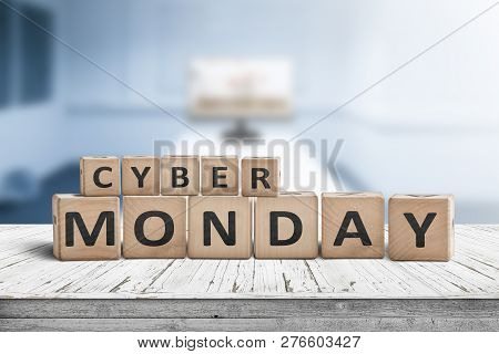 Cyber Monday Sign On A Wooden Desk With A Monitor In A Blue Room In The Background