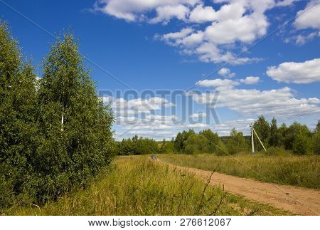 Perfect Sunny Summer Landscape With Green Grass, Dusty Rural Road And Bright Sky With White Clouds.