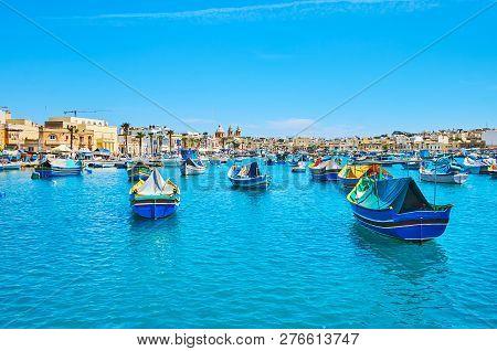 Enjoy The Lazy Walk Along The Marsaxlokk Harbour, Full Of Colorful Luzzu Boats, Rocking On The Gentl