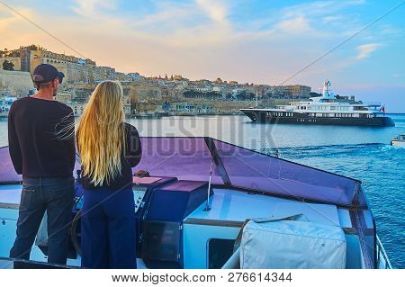 The Young Couple At The Helm Of Yacht With A View On Medieval Valletta Walls And The Cruise Ship On