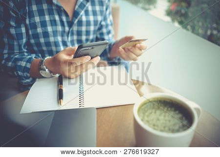 Man Using Mobile Smartphone And Credit Card For Online Shopping In Coffee Shop, Laptop Computer Note