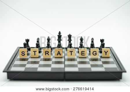 Wood Word Strategy Placed On Chessboard With A Chess Piece On The Back Negotiating In Business. As B
