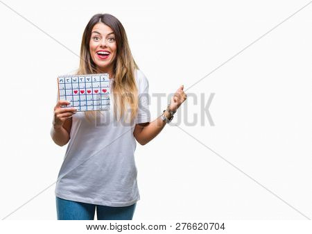 Young beautiful woman holding menstruation calendar over isolated background screaming proud and celebrating victory and success very excited, cheering emotion
