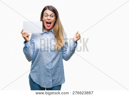 Young beautiful business woman holding blank card over isolated background screaming proud and celebrating victory and success very excited, cheering emotion