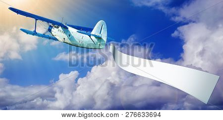 airplane with a white banner against a blue sky