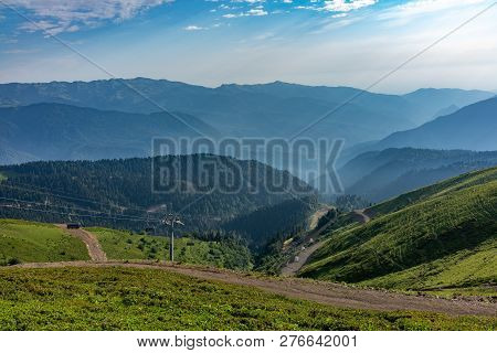 The Cable Car Goes Down From The Green Ridge. High Mountains In The Haze On The Horizon.