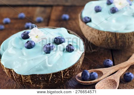 Blue Spirulina And Berry Smoothie Bowl, Fresh Fruit With Wooden Spoons Served In Coconut Bowls Over