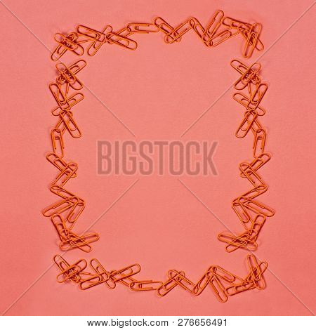Orange Paper Clip Frame Over Coral Color Paper Background With Free Space For Text. Image Shot From