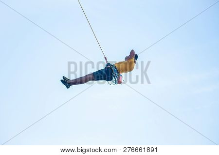 View Of Man Without Helmet Hanging On A Rope While Rappelling And Shows Flying Pirouettes In The Air