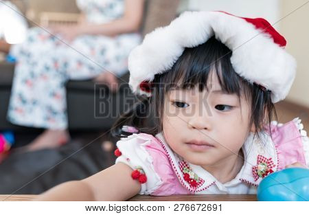 Little Daughter With Santa Hat Having Fun With Her Family At Home.
